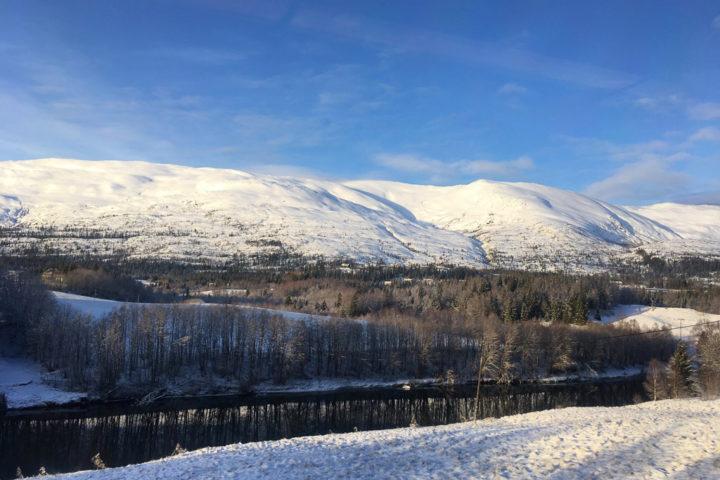 Ein Fluss vor einem Fjell im Winter an der Nordlandsbanen
