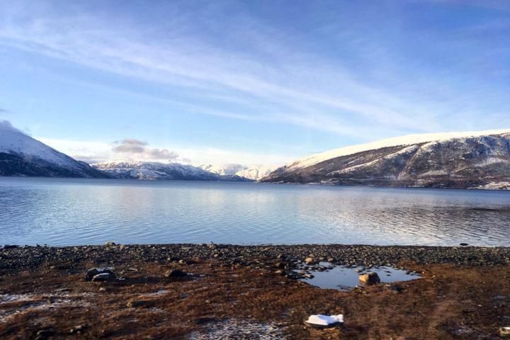 Ein Fjord vor einem Fjell im Winter an der Nordlandsbanen von Trondheim nach Bodø.